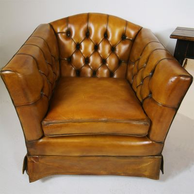 Pair of tan buttoned and skirted leather chairs.