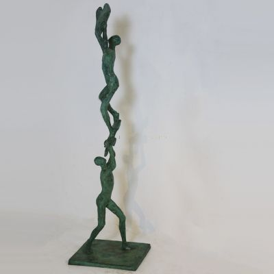 Modern art figurine depicting two figures creating a puzzle