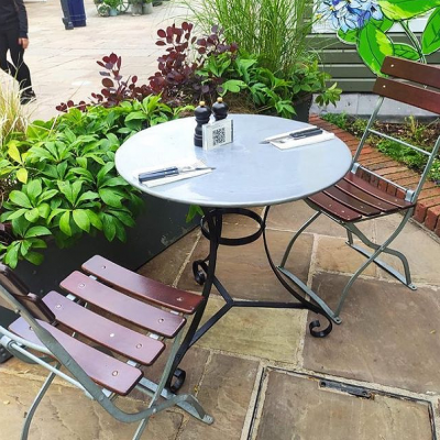 Round zinc topped garden table with painted metal base in a French style