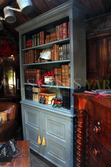 A Beautiful Hand Made Painted Book Case With Four Shelves Over Two Panelled Doors, Supported on Bracket Feet